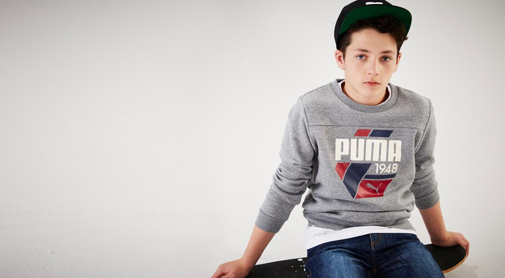 Boy sitting on on skateboard wearing Puma top