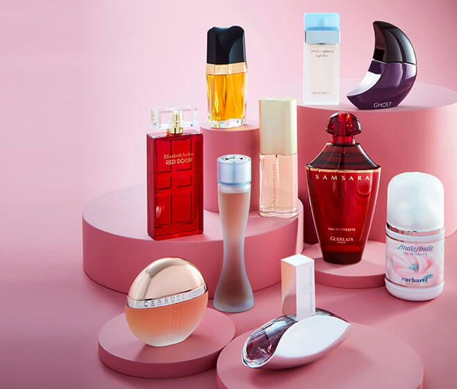 various fragrance bottles on pink background